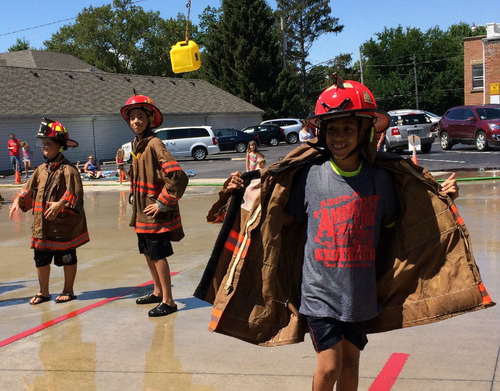 . Carol Harper � The Morning Journal <br> Eleven-year-old Brandon Noble, a sixth-grade student at Amherst Junior High, peels off turnout gear revealing an event t-shirt at Kids Water Fights at Amherst Fire Station at 414 Church St. in Amherst.