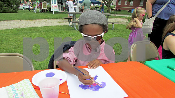 Jordyn Jackson, 9, of DeKalb concentrates on his painting Sunday at the Ellwood House Museum's annual Ellwood Summer Festival.