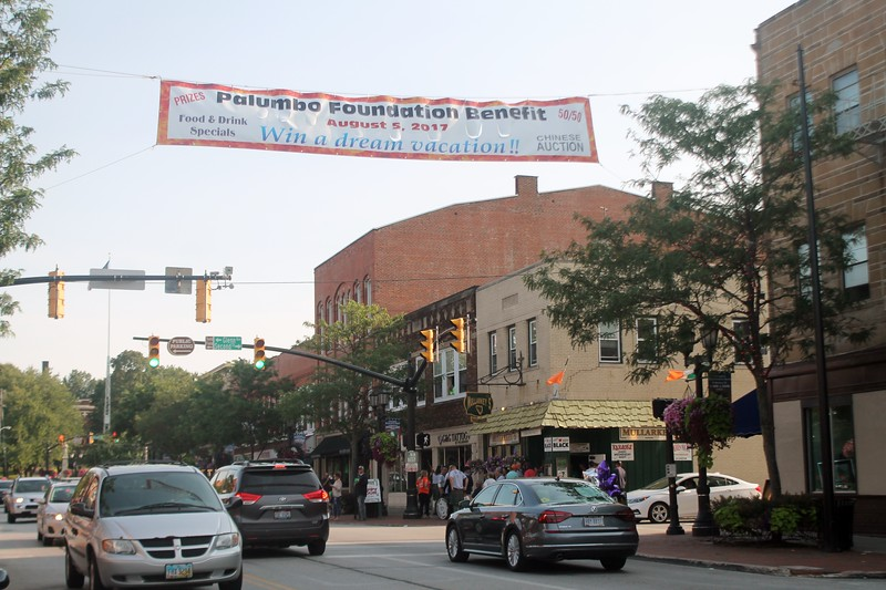 ​The Banner announcing the Second Annual Palumbo Pub Crawl hangs over Erie Street in Downtown Willoughby as people gather for the event.​ (Kristi Garabrandt/The News-Herald)