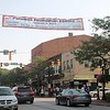 The Banner announcing the Second Annual Palumbo Pub Crawl hangs over Erie Street in Downtown Willoughby as people gather for the event. (Kristi Garabrandt/The News-Herald)