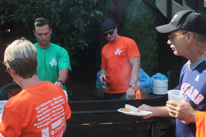 ​Nickleby's was one of the businesses participating in the event served up free burgers.​ Patrons grab burgers while drinking beer during the pub crawl. (Kristi Garabrandt/The News-Herald).