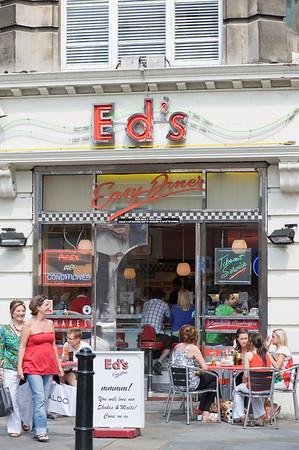People enjoy warm summer day in sidewalk cafe bars, West End, London, United Kingdom