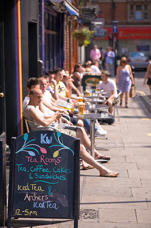 People enjoy warm summer day in sidewalk cafe bars, West End, London, United Kingdom
