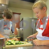 Reilly Farrell (left) and Joe Fuss (right), both from DeKalb, press garlic as part of a recipe as they prepare a dish in the Teens Can Cook culinary class Wednesday at the Leishman Center for Culinary Health at Kishwaukee Hospital.