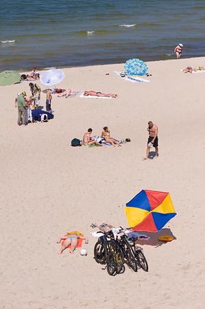 People enjoy hot summer day on sandy beach, Baltic Sea, Nida village, Neringa, Lithuania