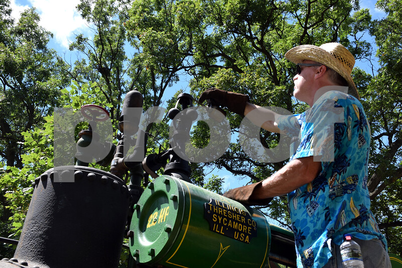 Katrina J.E. Milton - kmilton@shawmedia.com<br /> Mike Luse of Machesney Park performs maintenance on the Northern Illinois Steam Power Club's 1916 Illinois Thresher steam engine during the 61st annual Sycamore Steam Show and Threshing Bee on Friday at the Taylor Marshall Farm, 27707 Lukens Road in Sycamore.