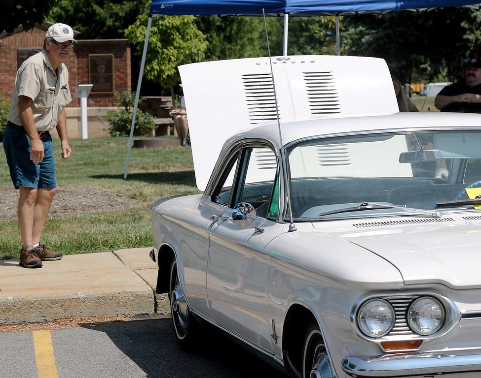 . Jonathan Tressler � The News Herald <br> Westlake resident Tom Reddy gives the engine compartmet of a 1964 Chevrolet Corvair belonging to Mentor-on-the-Lake residents Cindy and Doug Daugherty a thorough once-over during the Mentor Cruise-In auto show Aug. 11 at the city�s Civic Center Park.