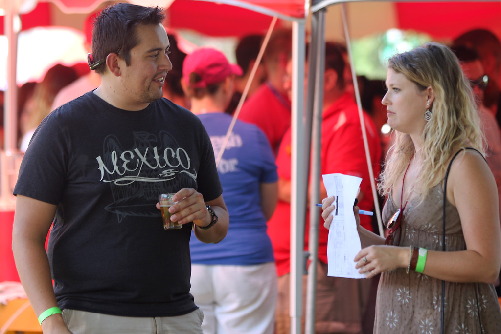 . Jonathan Tressler � The News Herald <br> Parma Heights resident Alex Krupa, left, and Marlene Thompson from Akron compare notes on the different brews they sampled during the 2018 Chardon Brewfest even on the city�s square Aug. 11.