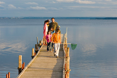 People relax on wooden pier overlooking Puck Bay, Hel Peninsula, Baltic Sea, Poland