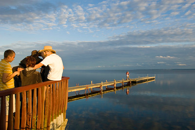 Young people relax by wooden pier overlooking Puck Bay, Hel Peninsula, Baltic Sea, Poland