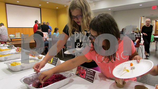 "Sophia Harder (left), 11, and Moriah Harder, 8, of DeKalb, try new fruits during the ""Funky Fruits"" event Saturday at the DeKalb Public Library."