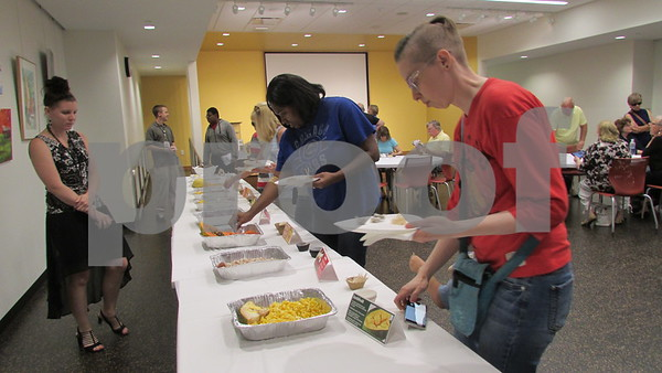"Aimee Barrows - for Shaw Media<br /> Patrons line up to try new fruits during the ""Funky Fruits"" event Saturday at the DeKalb Public Library."
