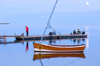 People relax on wooden pier overlooking Puck Bay, early evening, Hel Peninsula, Baltic Sea, Poland
