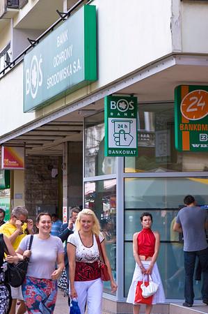 People on sidewalk passing bank, Lodz, Poland