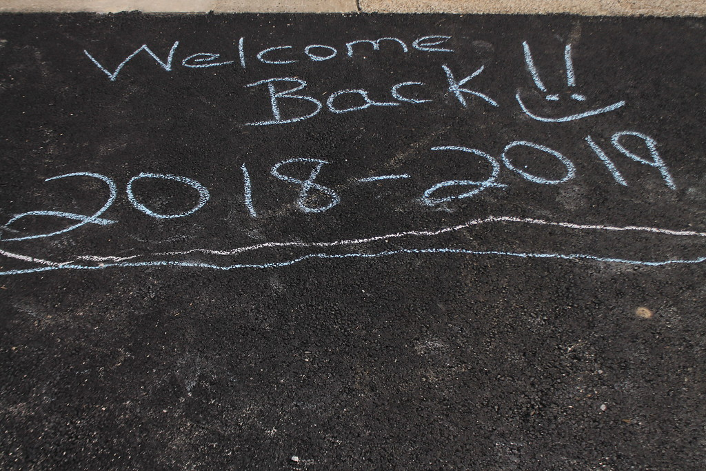 . A group of parents and students gathered at the Longfellow Elementary in Eastlake on Aug. 15, to draw inspirational messages on the school walkways to welcome the students back on their first day of school . Kristi Garabrandt-The News-Herald