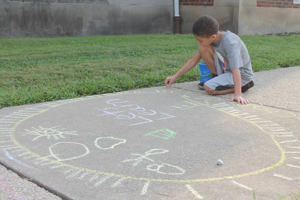 . Frederick Alexander, 8, was  part of  group of parents and students who gathered at Longfellow Elementary School in Eastlake on Aug. 15, to draw inspirational messages on the schools walkways to welcome students back on the first day of school. Kristi Garabrandt - The News-Herald
