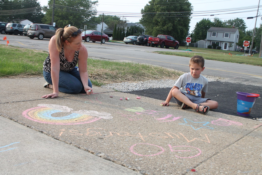 . Brandon Coliadis, 6, and his mom Jennifer  were  part of  group of parents and students who gathered at Longfellow Elementary School in Eastlake on Aug. 15, to draw inspirational messages on the schools walkways to welcome students back on the first day of school. Kristi Garabrandt - The News-Herald