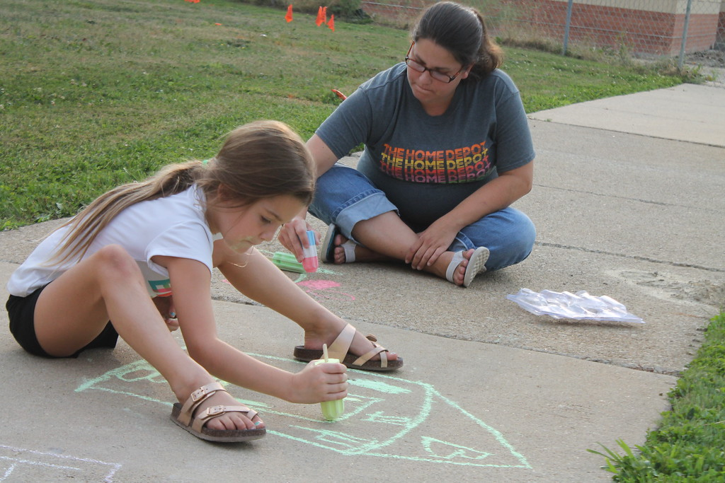 . Brooklyn Seghettti, 6, and her mom Jessica Earls  were  part of  group of parents and students who gathered at Longfellow Elementary School in Eastlake on Aug. 15, to draw inspirational messages on the schools walkways to welcome students back on the first day of school. Kristi Garabrandt - The News-Herald