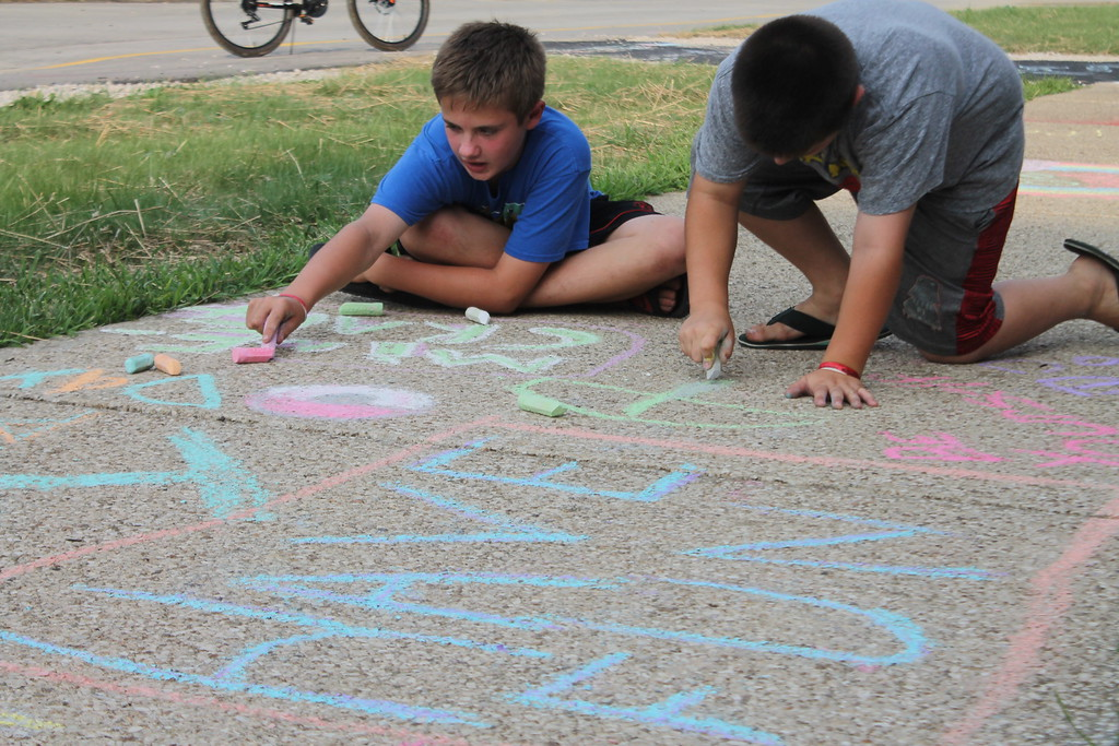 . Joey Galletti, 12, and his brother Andy were part of  group of parents and students who gathered at Longfellow Elementary School in Eastlake on Aug. 15, to draw inspirational messages on the schools walkways to welcome students back on the first day of school. Kristi Garabrandt-The News-Herald