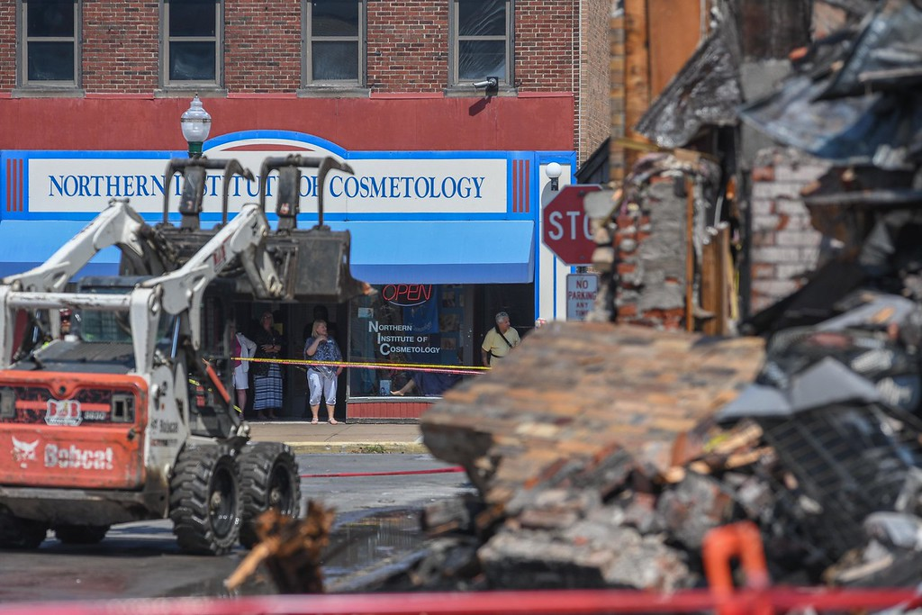 . Bystanders watch from the Northern Institute of Cosmetology as B & B Wrecking demolishes the rear portion of Thistle building at 700 Broadway Ave., Aug. 15, 2017. (Eric Bonzar/The Morning Journal)
