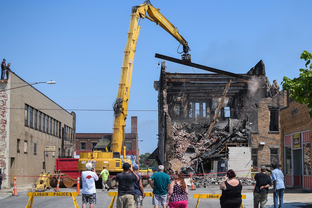 . Bystanders watch as B & B Wrecking demolishes the Thistle building at 700 Broadway Ave., Aug. 15, 2017. (Eric Bonzar/The Morning Journal)