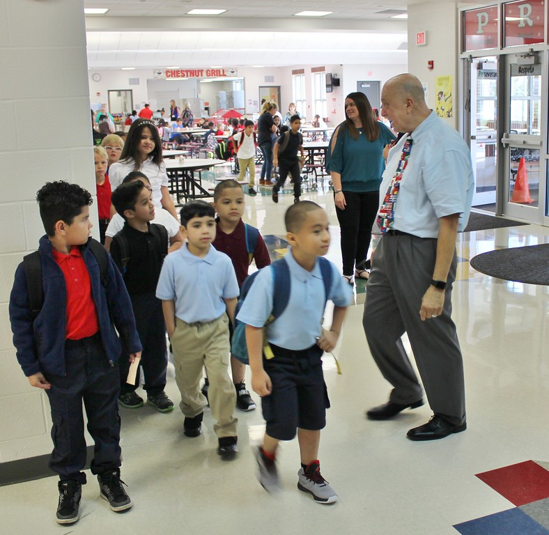 . Painesville Schools Superintendent John Shepard, right, greets Chestnut Elementary School students on the first day of school on Aug. 16. (Tawana Roberts � The News-Herald)
