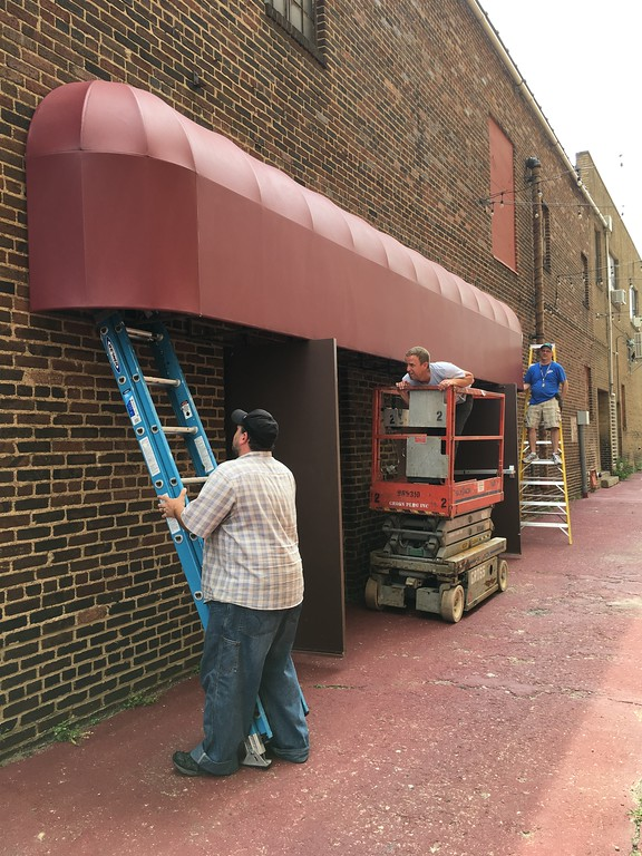 . Richard Payerchin - The Morning Journal  Lorain Palace Theater Technical Director Isaac Thompson, Theater Technician Andy Hartman and Maintenance Supervisor Ed Urban work to install the awning donated from Visual Expressions, 901 Broadway, on the north side of the theater on Aug. 15, 2018. The addition will become a cover for the Palace�s Sixth Street Experience gathering with drinks and music on Friday nights.