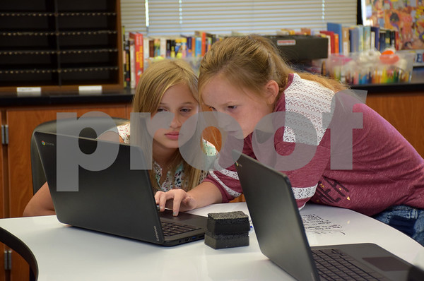 Katrina J.E. Milton - kmilton@shawmedia.com<br /> Indian Creek Middle School students Cheyenne Faye (left) and Allyssa Peterson explored their new Chromebooks on Wednesday in Joanne Burton's sixth-grade class on the first day of school. This was not only the first day of school for the students, it was also the first day in a new school building. The middle school changed locations from 425 S. Elm St. to the renovated and expanded Waterman Elementary School, 335 E. Waterman St.