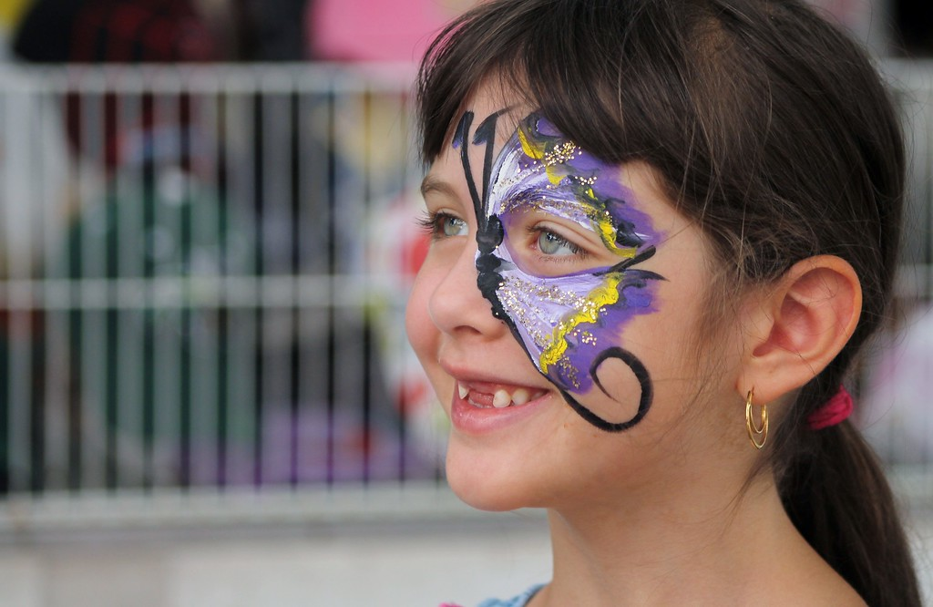 . Kristi Garabrandt � The News-Herald <br> Amanda Teter, 7, of Mentor, walks the fair with a purple butterfly painted on her face.�
