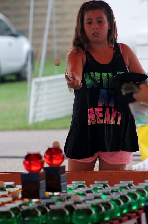 . Kristi Garabrandt � The News-Herald <br> Alana Cook, 10, of Mentor, attempts to win a gold fish by throwing balls into fish bowls.�