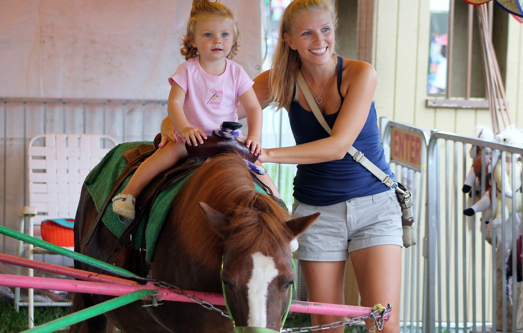 . Kristi Garabrandt � The News-Herald <br> Brooklyn Ruff, 1 1/2, of Madison enjoys the pony rides with her mom Leanna Ruff.�