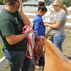 Kailee Leonard — The News-Herald <br> Jade Maldonado (left) and Anne Costello (right) help Zoey Brown prepare with her mini, Nugget for her in-hand barrel racing class.