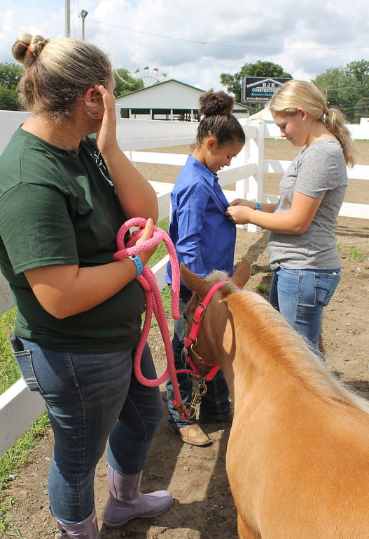 . Kailee Leonard � The News-Herald <br> Jade Maldonado (left) and Anne Costello (right) help Zoey Brown prepare with her mini, Nugget for her in-hand barrel racing class.