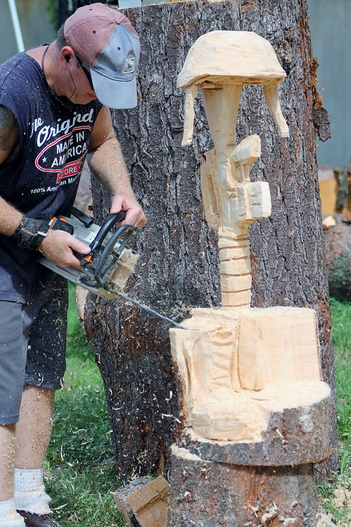 . Kristi Garabrandt � The News-Herald <br> Matthew Hannah owner of Insane Chain in Eastlake carves the Solder\'s Cross during his chain saw carving demonstration at the fair.�