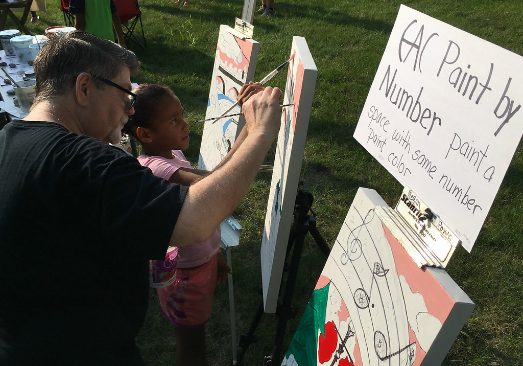 . Richard Payerchin � The Morning Journal  Elyria Arts Council volunteer Ron Nehls and Elyria resident Monica Allgood, 7, work on one of the paint by number canvases set out by the arts group at the inaugural Garford Arts Fest. The event brought food, artists and music to Kerstetter Way in downtown Elyria and hundreds turned out on Aug. 18, 2018.