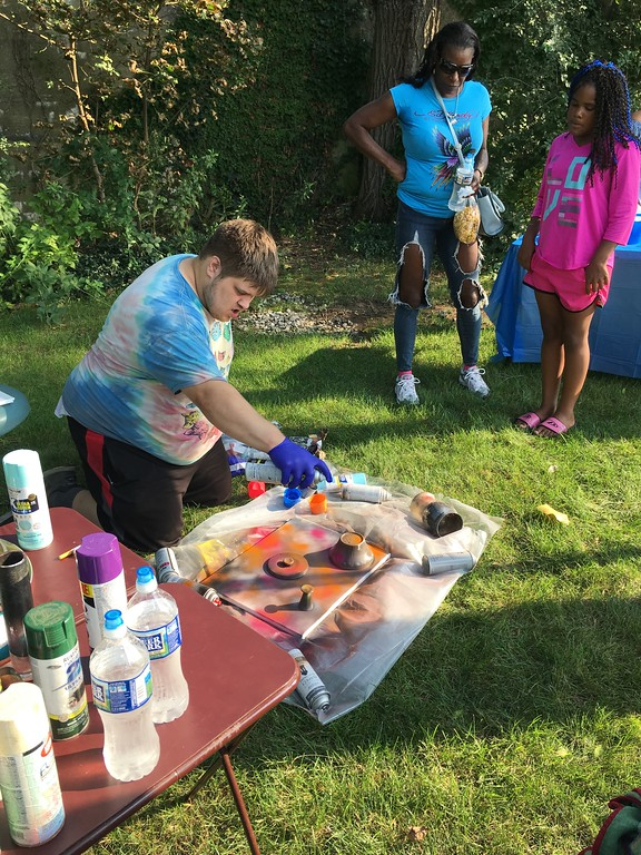 . Richard Payerchin � The Morning Journal  Artist Paul Pay uses spray paint to create a planetary outer space scene on canvas at the Garford Arts Fest, which brought food, artists and music to Kerstetter Way in downtown Elyria. Hundreds turned out for the inaugural festival on Aug. 18, 2018.