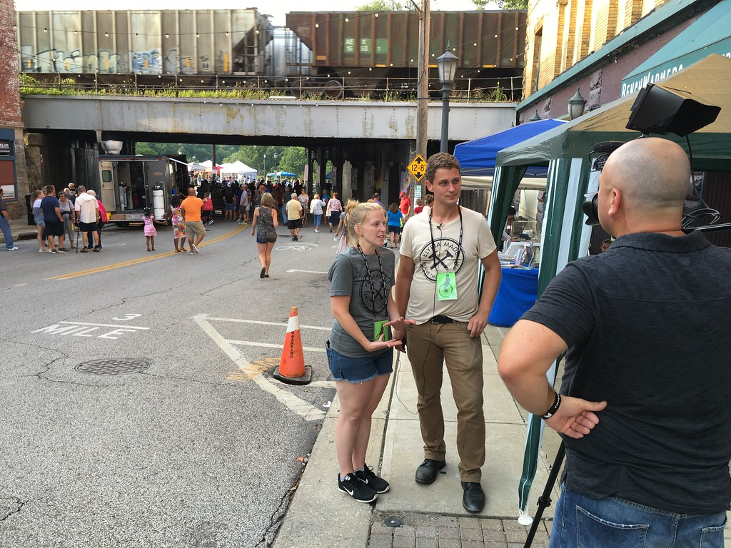 . Richard Payerchin � The Morning Journal   Garford Arts Fest co-organizers Andrea Repko and Steve Riggle speak for videographer Larry Reed while behind them people enjoy the festival and a train rolls overhead. Hundreds turned out for the inaugural festival on Aug. 18, 2018.