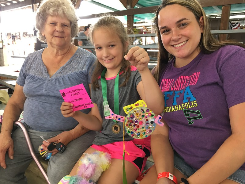 Richard Payerchin — The Morning Journal <br>&gt; Olivia Haponek, 8, of Wakeman, shows her crafted fish she used for the Cloverbud Show and Tell at the Lorain County Fair on Aug. 18, 2018. She is with her grandmother, Carol Burgos, and sister Kaitlyn Frazier, 18, a 4-Her and member of Firelands FFA.
