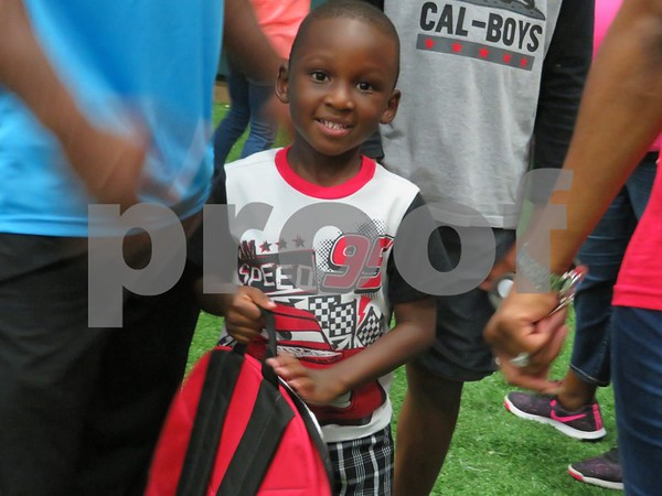 Katie Finlon for Shaw Media                               Hakeem Olaniran, 4, of DeKalb picks up a backpack to give to his cousin at the Back to School Bash on Saturday at the DeKalb Park District Sports and Recreation Center, 1765 S. 4th St.