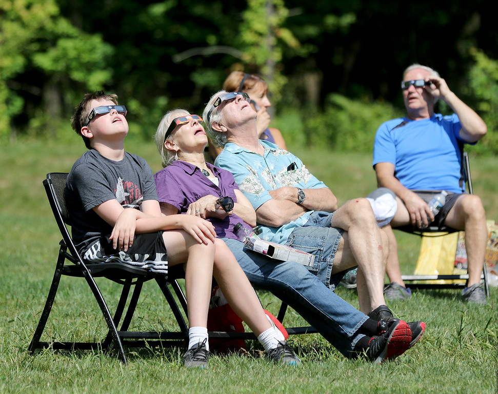 . Jonathan Tressler - The News-Herald <br> Visitors to the Geauga Park District\'s Observatory Park in Montville Township strike the day\'s most popular pose as the sun reaches the 80 percent coverage Northeast Ohio viewers saw around 2:30 p.m. Aug. 21.