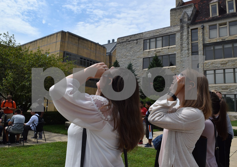 Katrina J.E. Milton - kmilton@shawmedia.com<br /> Northern Illinois University graduate students in the School of Psychology Elyse Doll (left) and Annie Phelan observe a partial solar eclipse on Monday, Aug. 21, at the fountain courtyard east of Davis Hall on the NIU campus.