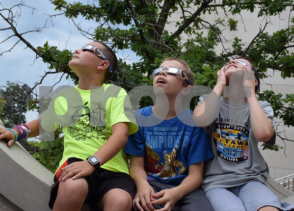 Katrina J.E. Milton - kmilton@shawmedia.com<br /> Ian Wickens-Walther (from left), 10, Levi Grych, 10, and Joseph Marchese, 9, observe the partial solar eclipse while wearing eclipse glasses at the DeKalb Public Library on Monday, Aug. 21.