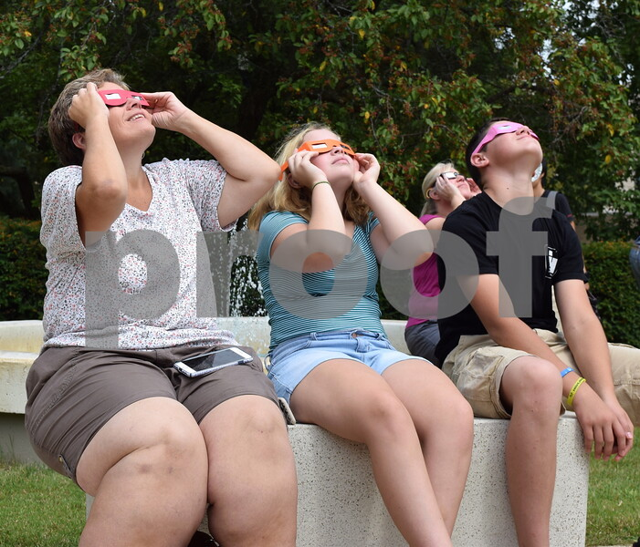 """Katrina J.E. Milton - kmilton@shawmedia.com<br /> Lisa Kaczmarczyk of DeKalb (left), her daughter Regina, 12, and their neighbor Dylan Callaghan, 15, wear solar eclipse glasses to observe the partial solar eclipse on Monday, Aug. 21. """"I remember seeing the last solar eclipse when I was my daughter's age, so I took the day off of work so that we could all view the eclipse together,"""" Kaczmarczyk said."""