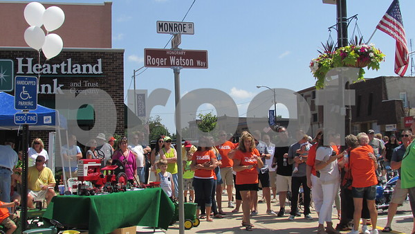 "Family and friends gather around the newly dedicated ""Roger Watson Way"" during the Cruisin' to Genoa Car Show on Saturday in Genoa.  Aimee Barrows for Shaw Media"