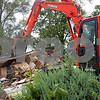 Christopher Heimerman – cheimerman@shawmedia.com<br /> An excavator finishes bringing down the walls of a house near the corner of state Route 64 and Airport Road on Tuesday in Sycamore. Sycamore City Manger Brian Gregory said the Sycamore Park District owns the property and will collaborate with the DeKalb County Forest Preserve District to landscape the space.