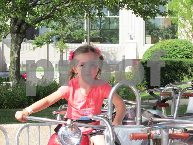 Drew Zimmerman – dzimmerman@shawmedia.com<br /> Maycee Kidd, 5, of DeKalb rides on one of the rides at DeKalb's 40th annual Corn Fest, which kicked off on Friday.