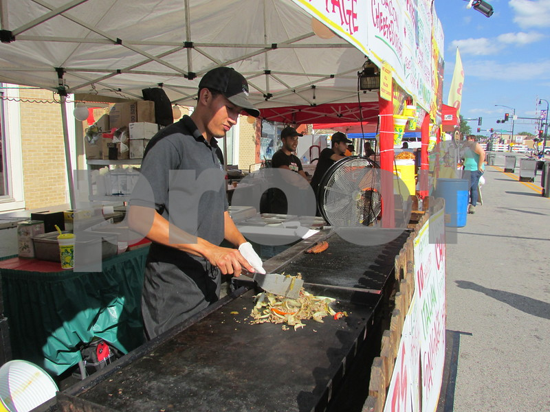 Drew Zimmerman – dzimmerman@shawmedia.com<br /> David Hernandez of Genoa Italian Concessions prepares a Philly Cheesesteak during the 40th annual DeKalb Corn Fest, which kicked off on Friday.