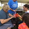 Richard Payerchin - The Morning Journal <br> Lorain County Dog Kennel volunteers, from left, Edie Becker, Tory Mittler, Bella Huffman and Alexa Huffman work on the harness and leash of a dog on Aug. 26, 2017, at the Lorain County Dog Kennel's first Dog Appreciation Day. The kennel had six dogs adopted and one claimed by its owner during the event, meant to connect families to new pets and raise awareness of the mission of the facility.