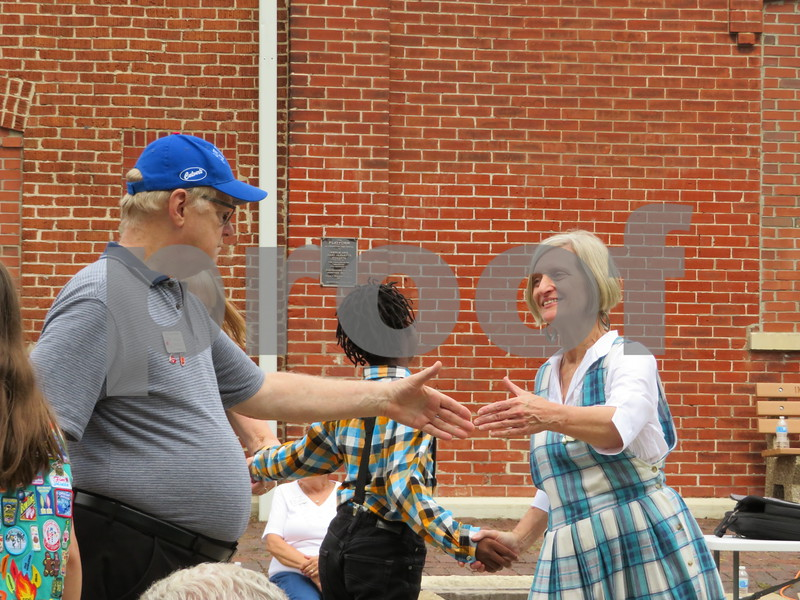 Katie Finlon for Shaw Media<br /> Christi Slavenas, a board member on the Kishwaukee Valley Heritage Society and Genoa resident, square-dances with other patrons at Pioneer Day on Sunday in Genoa.