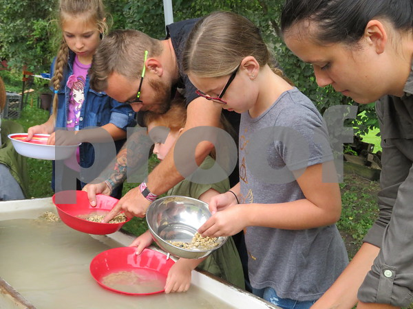 Katie Finlon for Shaw Media<br /> Bryan Jensen (far left) and Ellyn Clark (far right) help Gabby (inner left) and Faith Jensen (inner right), 4 and 9, pan for gold at Pioneer Day on Sunday in Genoa.